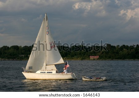 man sailing boat with attached dinghy