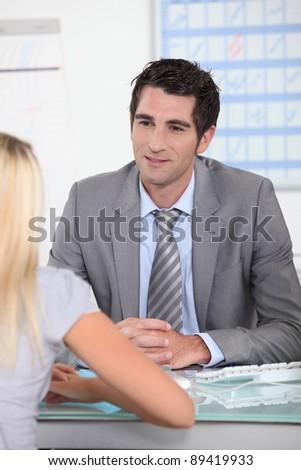 Man sat at desk talking to blond female - stock photo