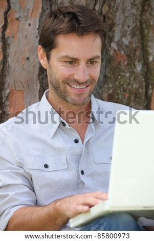 Man sat by tree with laptop computer