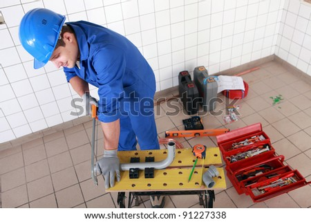 Man sawing plastic pipe to size