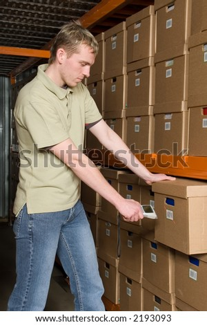Man scanning barcode on the box in the warehouse