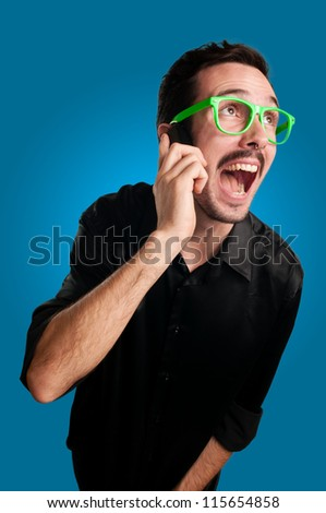 man screaming at the telephone on blue background - stock photo