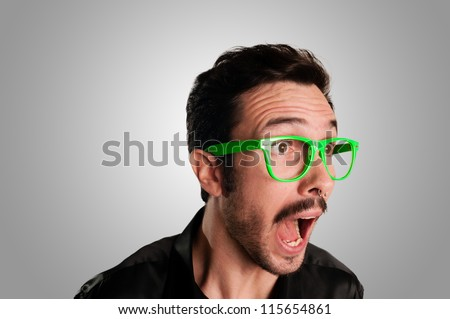 man screaming with green eyeglasses on grey background