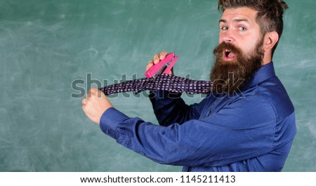 Man scruffy use stapler dangerous way. Hipster teacher formal wear necktie holds stapler. School stationery. Teacher bearded man with pink stapler chalkboard background. School accident prevention.