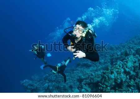 Man scuba dives in open ocean