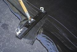 Man sealing asphalt driveway/Sealcoating selective focus