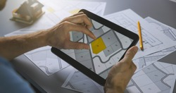 man searching building plot to buy on cadastral plan for house construction on digital tablet