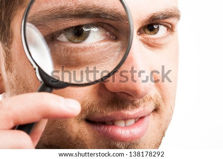 Man searching for something using a magnifying glass
