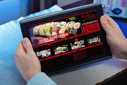 man searching website internet restaurant to purchase food online with tablet in you home / hands of a man in a website of a restaurant food delivery service in the tablet