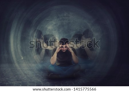 Man seated on the floor, hands to head, suffer split emotions into different inner personalities. Multipolar mental health disorder. Schizophrenia psychiatric disease. Dementia reactions mood change.