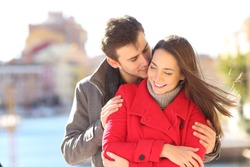 Man seducing a woman whispering on ear in a town street in winter holiday