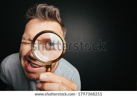 man see through magnifying glass on the black backgrounds. Big man eye Сток-фото ©