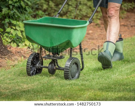 Man seeding and fertilizing residential backyard lawn with manual grass seed spreader.
