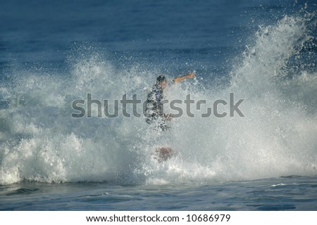 Man seems to walk on water as he wipes out in rough wave.  Water splashing and flying droplets fill screen.