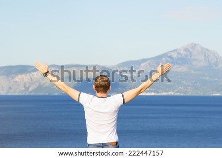 Man seen from behind, looking seaward or ocean. The man raised his hands up against the mountains. Male tourist traveler raised his hands up. Joy of freedom, the fresh sea air. Everything is fine.