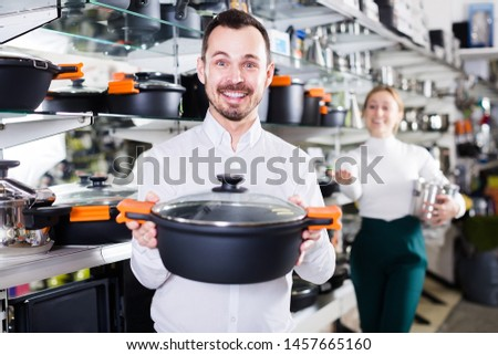 Man sells different kinds of saucepan in a crockery store