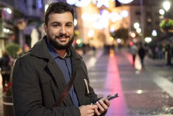 Man sending and looking social network messages in winter christmas images in the city