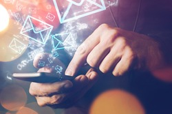 Man sending e-mail message to mailing list contacts using smartphone, close up of hands holding phone.