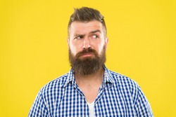 Man serious face raising eyebrow not confident. Have some doubts. Hipster bearded face not sure in something. Doubtful bearded man on yellow background close up. Doubtful expression. Need to think.