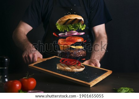Man serving a delicious layered burger on a serving board Stock photo ©