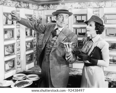 Man serving a dish to a woman in an Automat