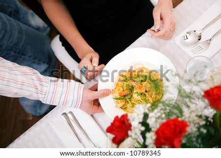 Man serving woman a plate of pasta, domestic setting (selective focus on the food)