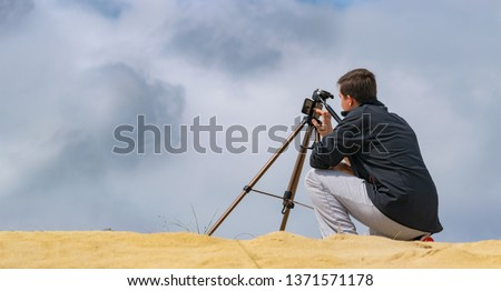 Man setting up mobile phone on tripod for photography and video making in sand hills. Cloudy sky on background. Travel photographer concept.