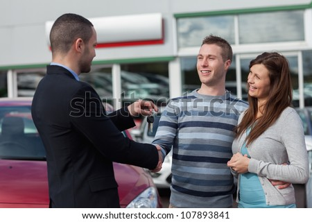 Man shaking hand with salesman in a dealership