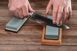Man sharpening a Japanese knife with a whetstone on a wooden table. Beautiful wavy pattern of Damascus steel blade.