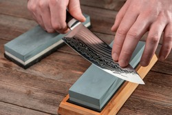 Man sharpens a Gyuto knife using a whetstone on a rustic wooden table. Japanese knife with Damascus steel.