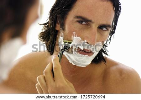 Man shaving face in mirror
