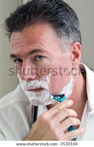 Man shaving trying to get ready for work.