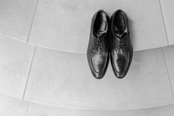 Man shoes on floor close up black color. Expensive shining polished leather male shoes standing at neutral wooden floor background with space for text overlays slow tracking no people