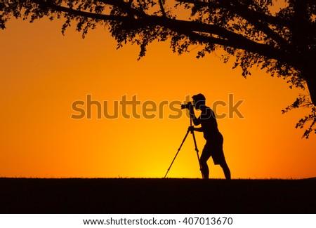 Man shooting a camera in a beautiful natural setting.