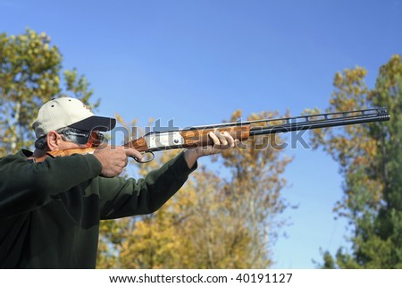 Man shooting a shotgun. With trees in background.