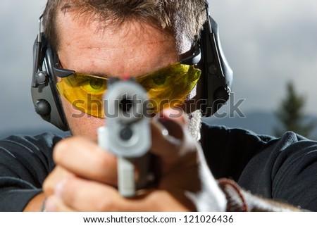 Man shooting on an outdoor shooting range, selective focus - stock photo