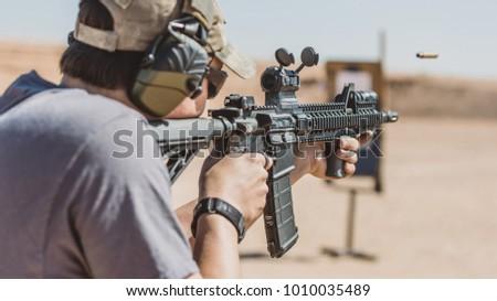 Man shooting rifle on desert range medium shot shell ejecting