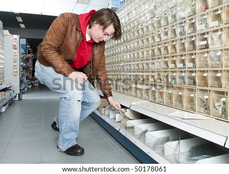 Man shopping for tools, materials and fasteners at a hardware store