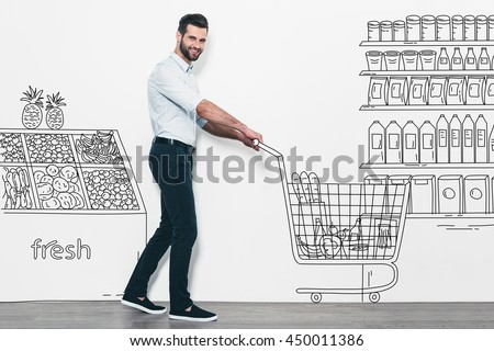Man shopping. Handsome young smiling man walking in front of the white wall with pencil drawn supermarket and shopping cart on it