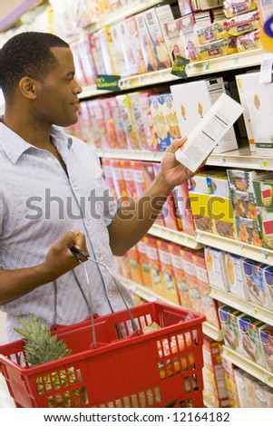 Man shopping in supermarket checking contents of box