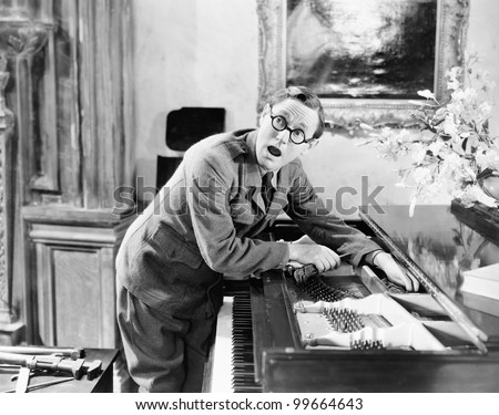 Man shouting with his hand caught in a piano