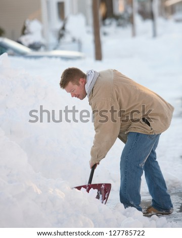 Man shoveling snow from street in winter