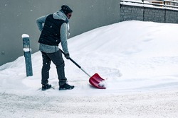 Man shoveling snow outside with a snow shovel in winter