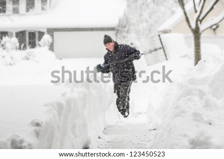 Man shoveling snow (shallow depth of field, focus on snow in foreground)