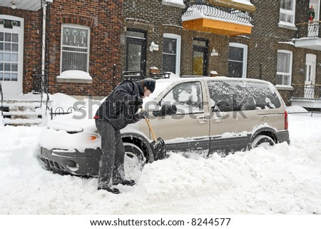 Man shovelling and removing snow from his car during a snow storm.