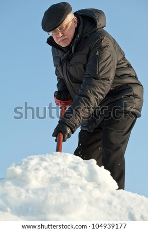 Man shovelling fresh snow from a road after hard snowfall