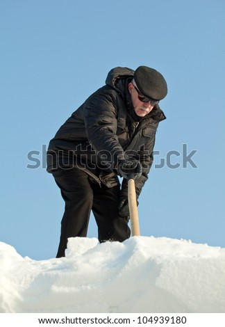Man shovelling fresh snow from a roof after snowfall