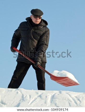 Man shovelling fresh snow from a roof after snowfall with a red shovel