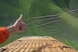 man showing a Like from the basket of balloon on the green earth background, top view. Armenia