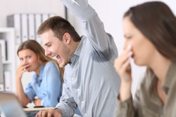 Man showing a sweaty and stinky underarm and disgusted colleagues at office